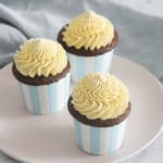 A photo of three cupcakes topped with french buttercream
