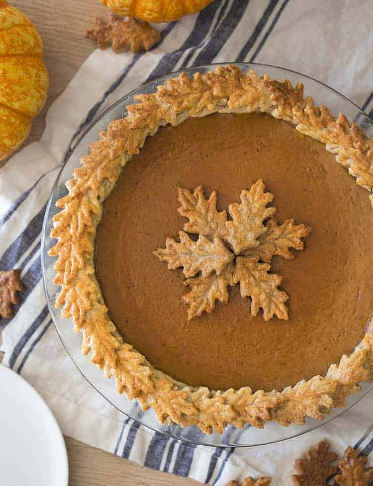 A pumpkin pie with leaved on the edge made of pastry