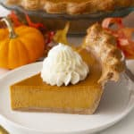 A piece of pumpkin pie topped with a big dollop of whipped cream