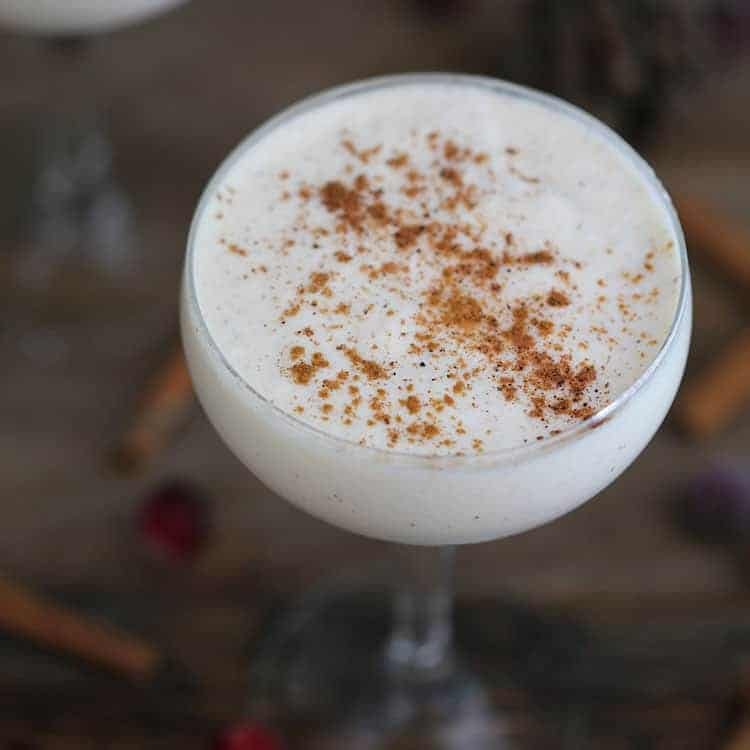 a coupe glass filled with eggnog on a wooden table