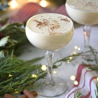 eggnog in a coupe glass next to Christmas lights and greens
