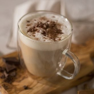 A photo of a latte with cinnamon and chocolate in a glass mug.