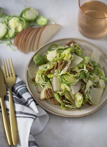 A photo of a shaved Brussel Sprouts salad on a plate ready to be served.