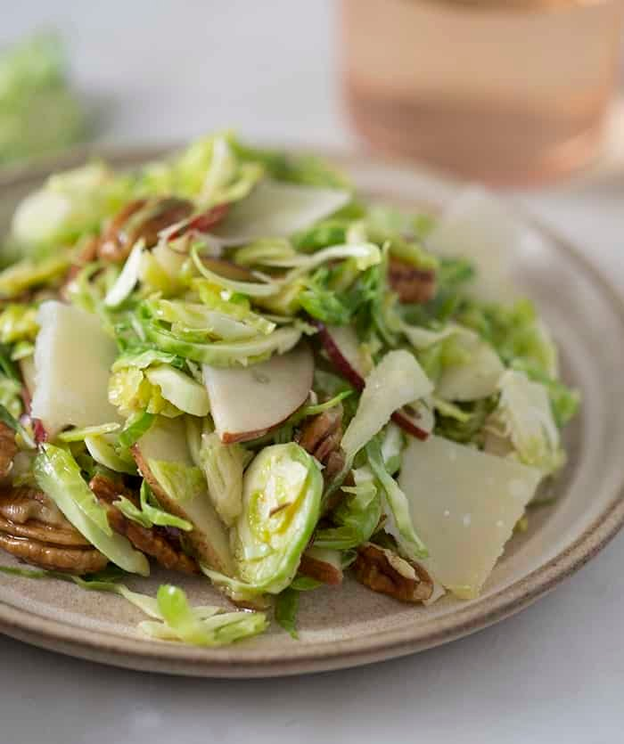 A photo of a Brussel sprouts salad with pecans, pears and shaved parmesan.