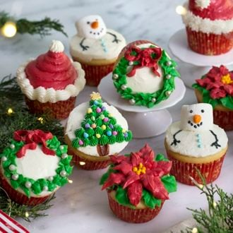 A photo of an assortment of Christmas cupcakes on a white marble table