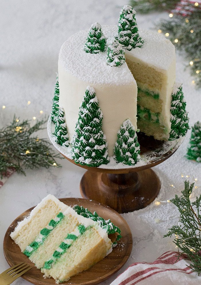 A photo of a christmas tree cake covered in buttercream pine trees and dusted with powdered