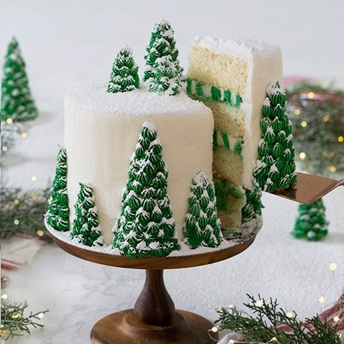A photo of a cake covered in buttercream pine trees