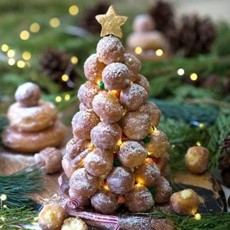 A photo of a croquembouche surrounded by evergreen cuttings and mini lights