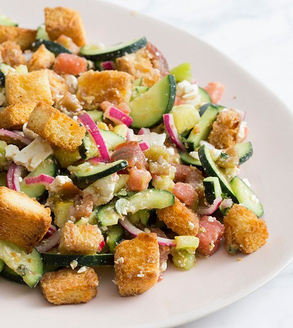 A photo of a panzanella salad on a serving plate.