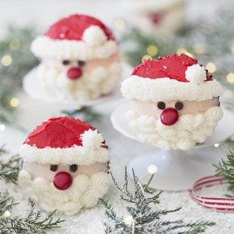 A photo showing a group of Santa cupcakes on a white marble table with greenery.