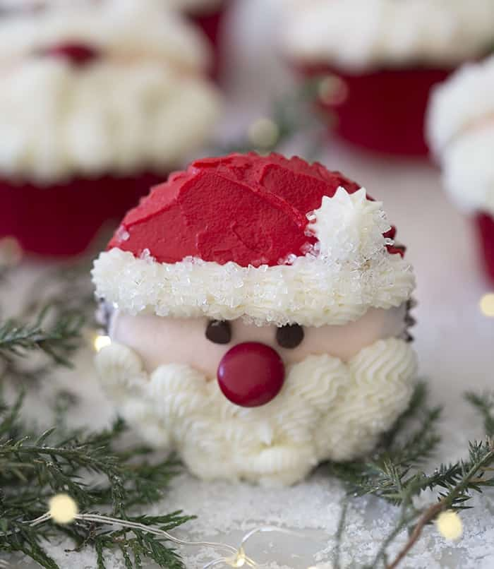 A close up phot showing a santa cupcake surrounded by Christmas lights