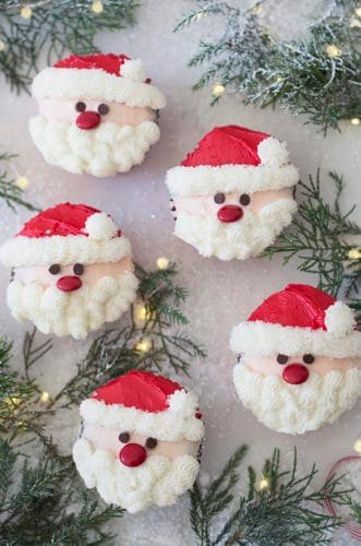 A photo showing a group of santa cupcakes on a white marble table with Christmas lights and evergreens