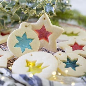 Stained glass cookies hanging from holly branches.