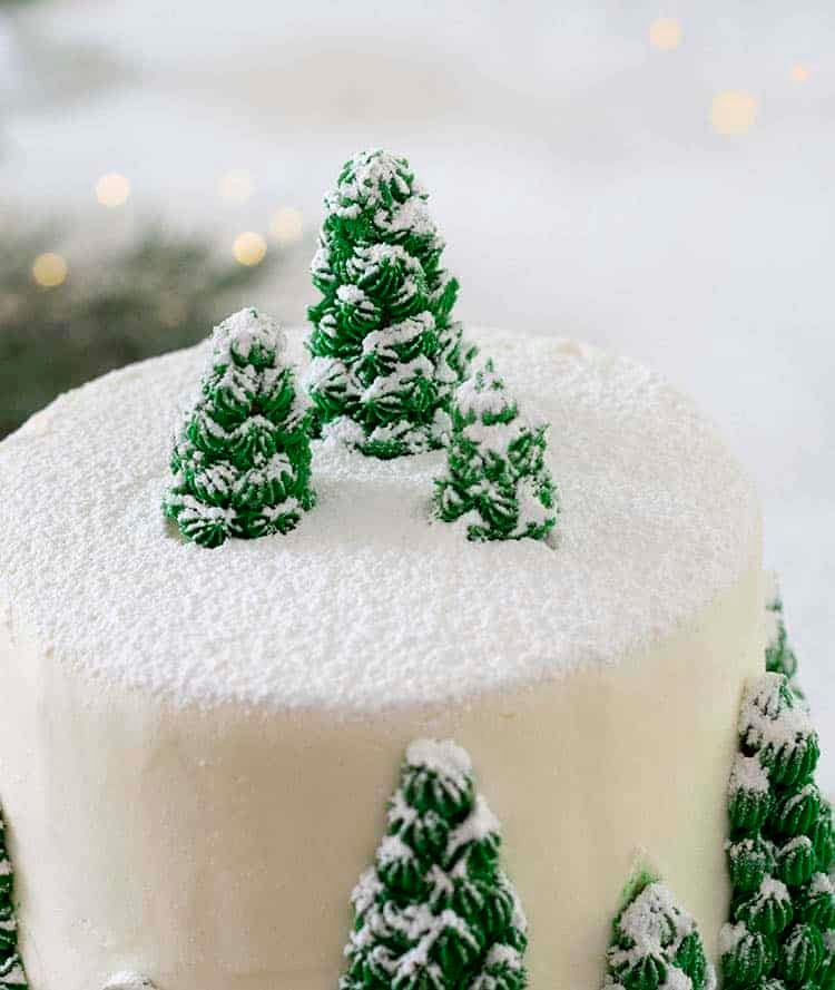 A close up photo of a Christmas cake with little pine trees rendered in buttercream and dusted with powdered sugar.