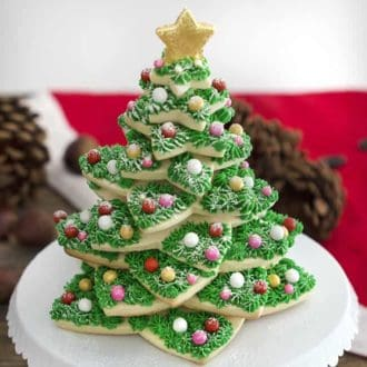 A Christmas Cookie tree on a white cake stand.
