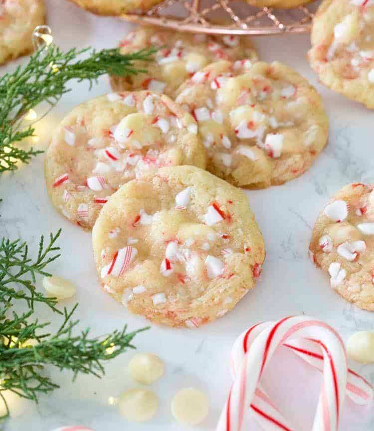 A group of white chocolate peppermint cookies next to candy canes and evergreen clippings.