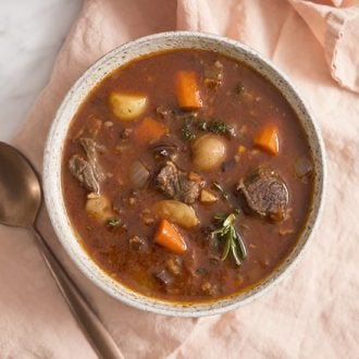 A photo of a bowl of beef stew on a pink linen napkin