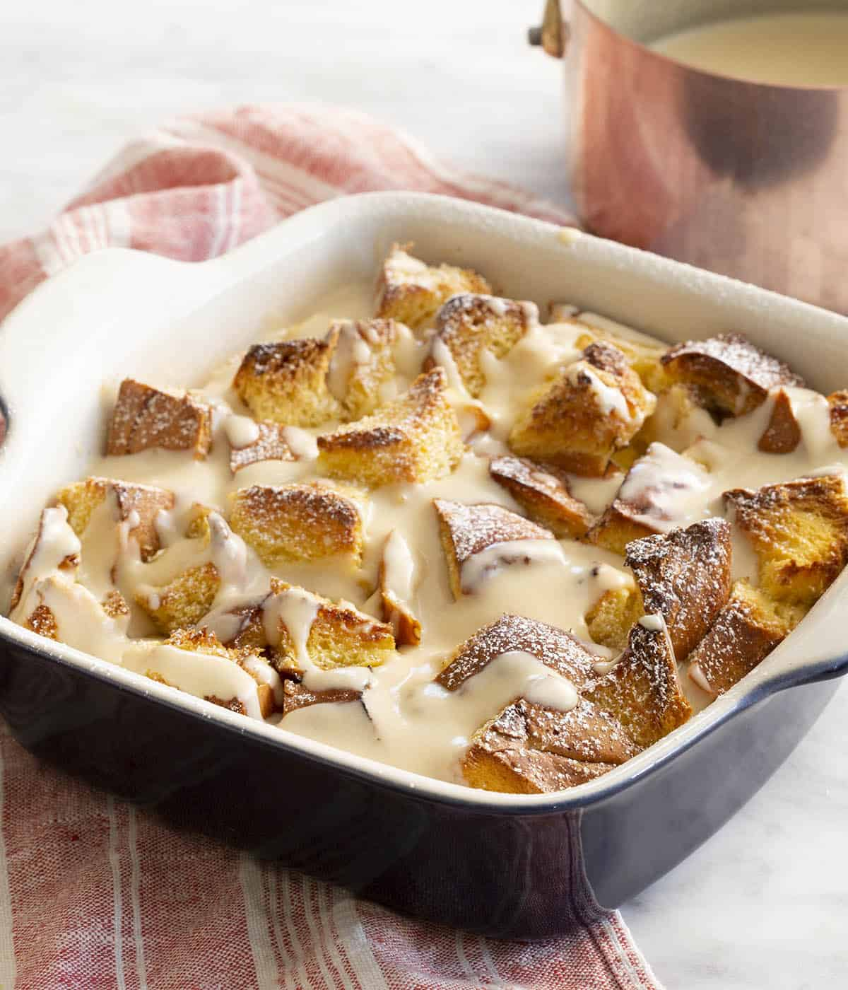 Bread pudding topped with rum sauce in a square baking dish.