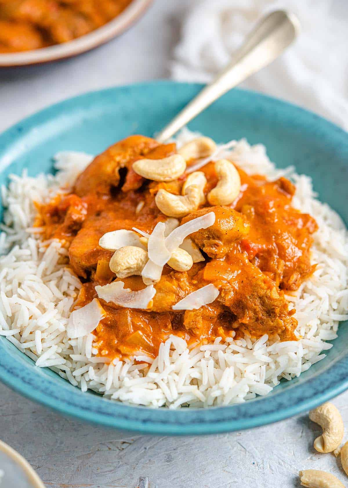 A close up of butter chicken in a bowl with rice