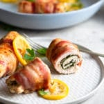 A photo showing bacon-wrapped chicken stuffed with spinach on a white plate