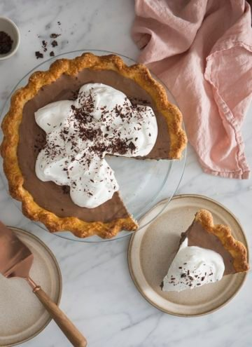 A top down photo of a chocolate pie covered in whipped cream and shaved chocolate.