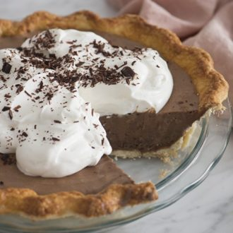 A photo of a chocolate pie with a piece taken out.