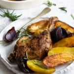 A photo of roasted duck legs with onion and potatoes on a plate.
