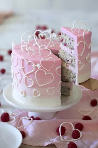 A photo of a pink ombré heart cake on a white marble table.