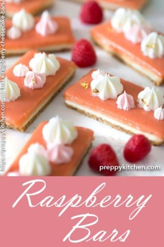 A clipping of raspberry bars with dollops of Swiss meringue buttercream on top.