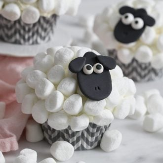 A closeup photo of a sheep cupcake with a black fondant face and mini marshmallow wool