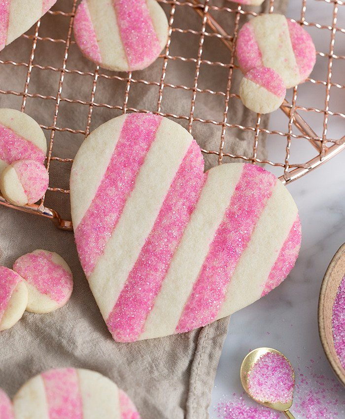A photo of a pink and white striped Valentine's Day Heart Cookie with sparkling pink sanding sugar on the pink stripes