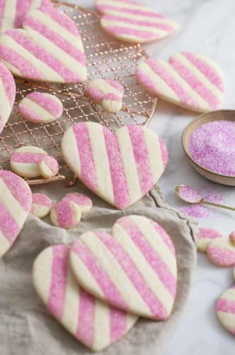 A photo showing a group of striped pink and white Valentine's Day Heart Cookies on a white marble surface