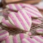 A close up photo of a pink and white striped valentine's day sugar cookie shaped like a heart.