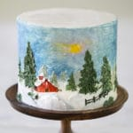 A photo showing a cake painted of a winter scene with a snow covered barn