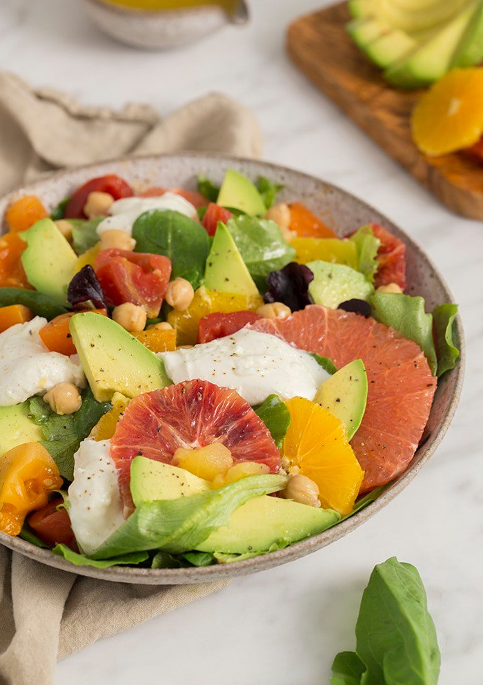 A photo of an avocado salad with various citrus premiums and burrata in a white bowl