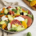 A photo of a colorful avocado salad with oranges and greens