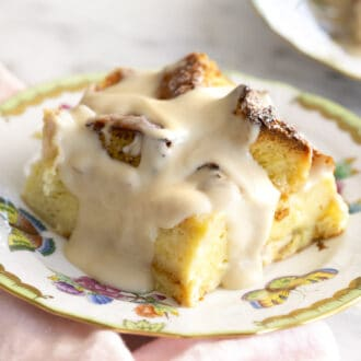A piece of bread pudding dripping with sauce on a porcelain plate.