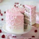 A pink ombré cake covered in white candy melt hearts.