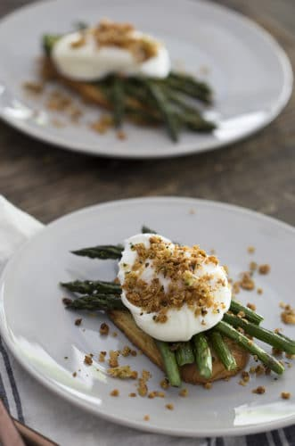 A photo of two plates on a wooden table with poached eggs on asparagus and toast.