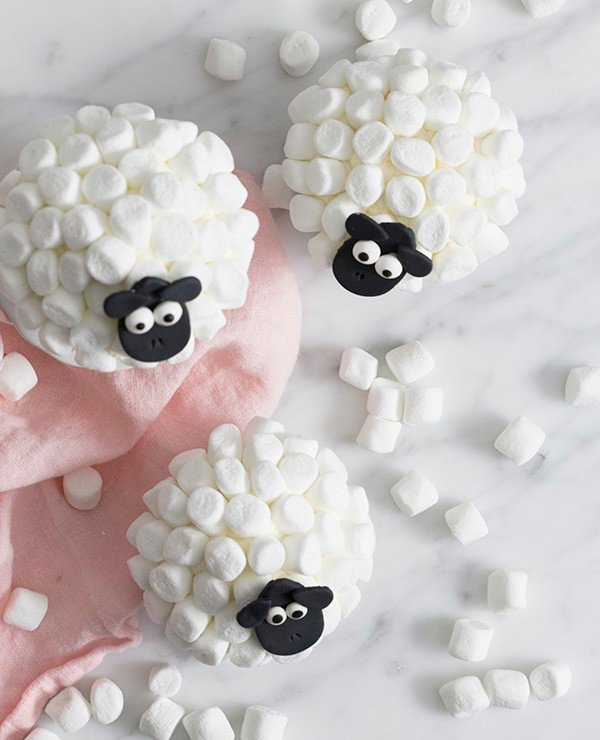 A top down photo of a group of cute sheep cupcakes on a white marble surface