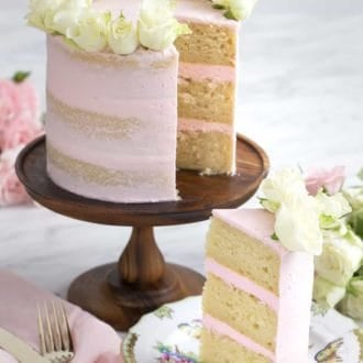 three layer vanilla cake with pink frosting topped with flowers