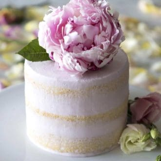 three layer vanilla cake with pink frosting topped with a flower