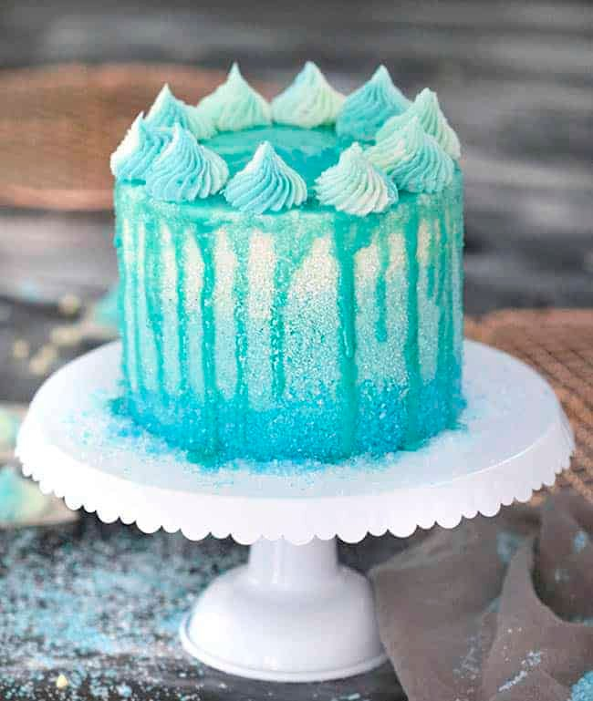 A winter wonderland cake covered in blue sparkles with a blue drip.