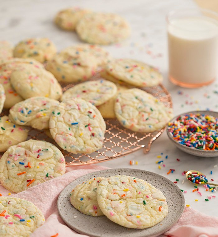 A photo of many white cake mix cookies on a copper cooling rack