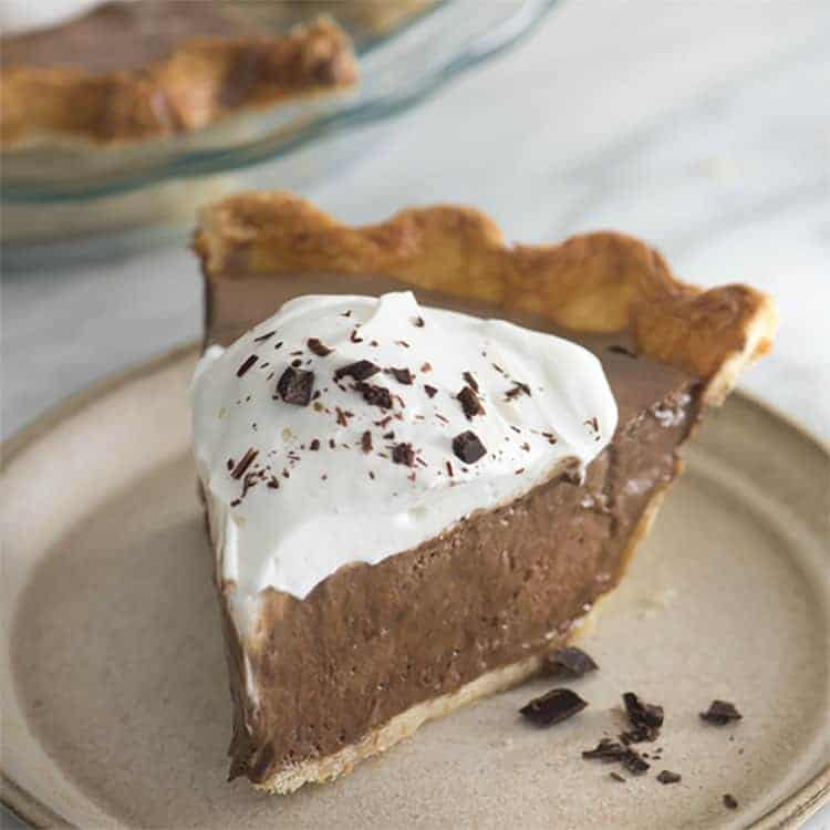 A piece of chocolate pie topped with whipped cream and shaved chocolate