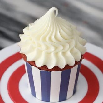 A close up photo of a cupcakes topped with a beautiful piped dollop of cream cheese frosting.