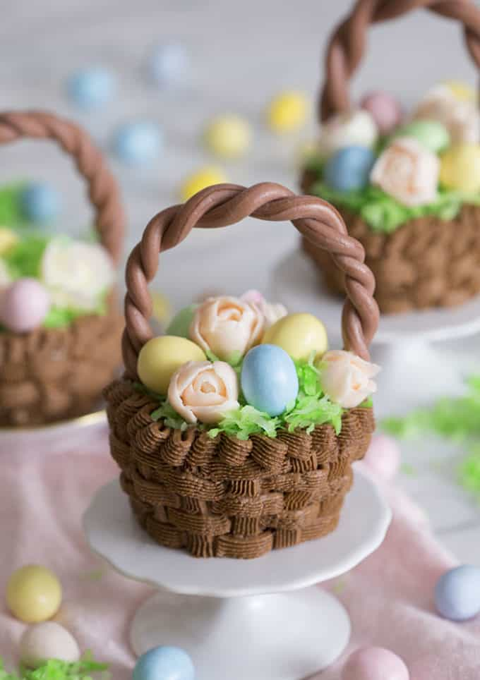 A cupcake that looks like an easter basket filled with flowers and eggs