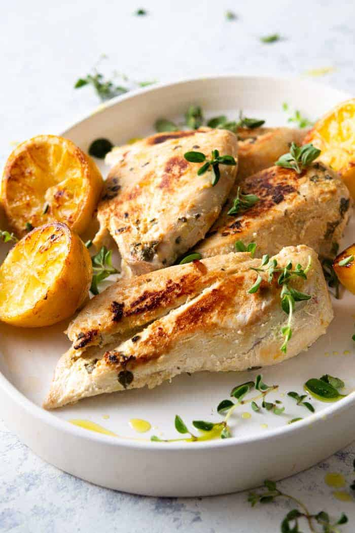 Greek chicken on a serving plate with oregano and charred lemons