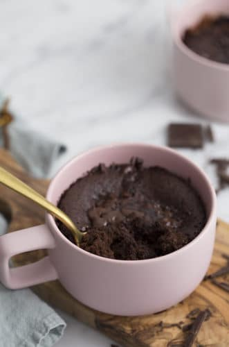 A photo of a chocolate cake in a pink coffee mug