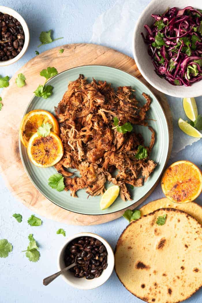 An overhead shot of slow cooker pork carnitas on a blue plate with tortillas and toppings